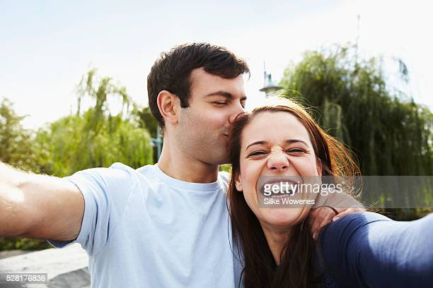 Portrait of couple taking selfie in park