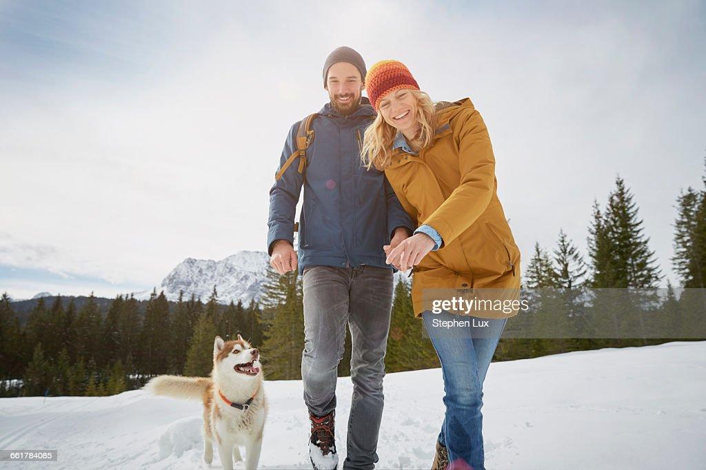 Portrait of couple walking husky in snow covered landscape, Elmau, Bavaria, Germany : Stock-Foto