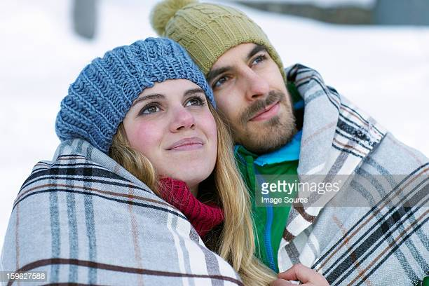 portrait of couple wearing knit hats, wrapped in blanket - ピンクの頬 ストックフォトと画像