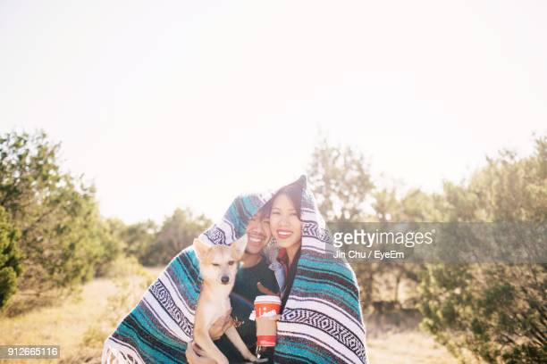 portrait of couple with dog wrapped in blanket against trees against clear sky - shiba inu winter stock pictures, royalty-free photos & images