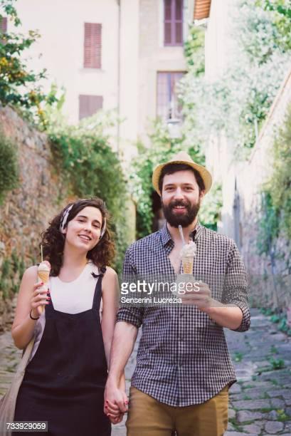 Portrait of couple with ice cream cones on cobbled street, Arezzo, Tuscany, Italy