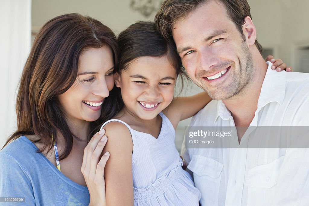 Portrait of couple with one child smiling : Stock Photo