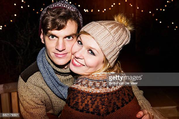 portrait of couple with wooly hats outdoors.
