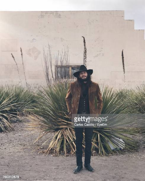 Portrait Of Cowboy Standing By Plant Against Wall