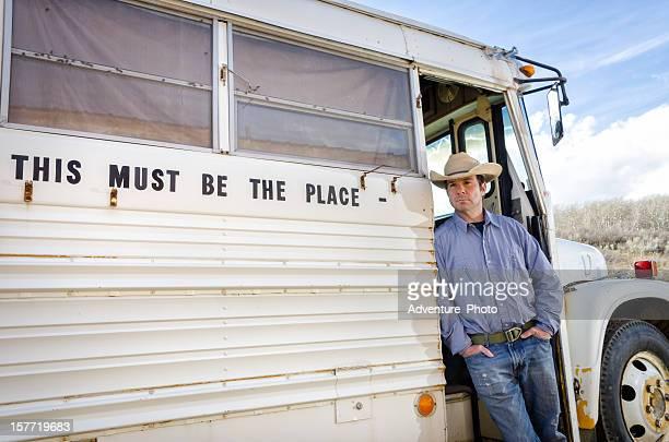 Retrato de Cowboy pé junto à Old School Bus ao ar livre