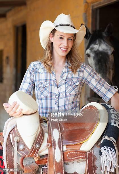 portrait of cowgirl holding saddle - hugh sitton - fotografias e filmes do acervo