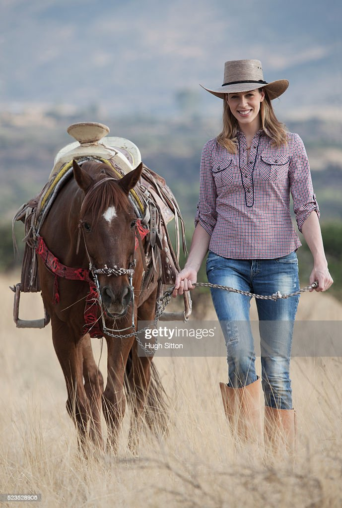 Portrait of cowgirl leading horse : Stock Photo