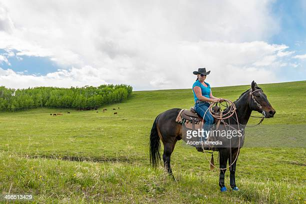 Portrait of cowgirl on open range, cattle behind
