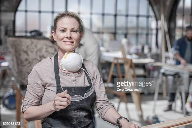 Portrait of craftswoman holding safety goggles in antique restoration workshop