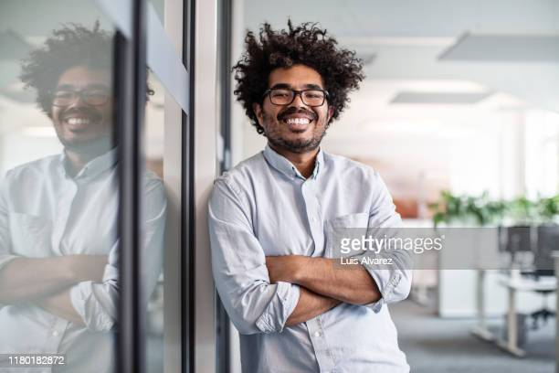 portrait of creative businessman leaning on wall in office - mid adult men stock pictures, royalty-free photos & images