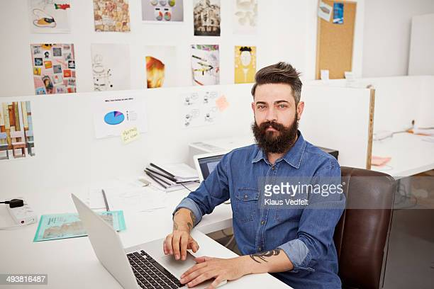 Portrait of creative businessman sitting by desk
