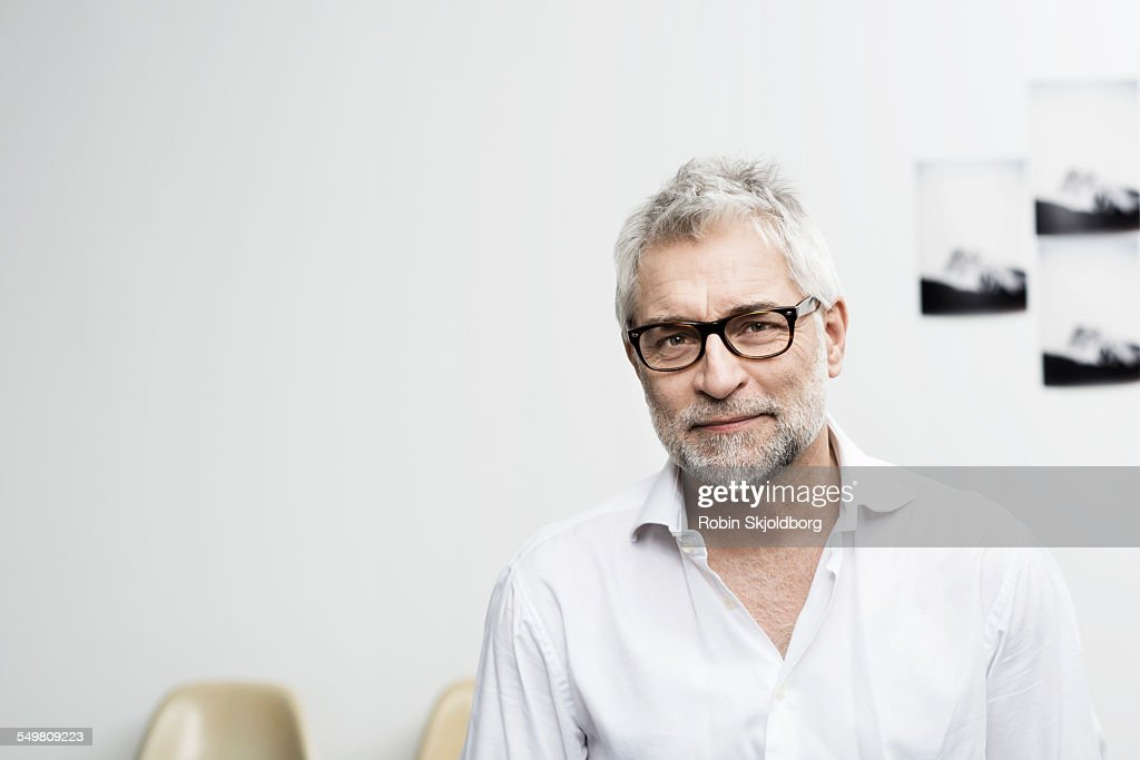 Portrait of creative grey haired man with glasses : Stock Photo