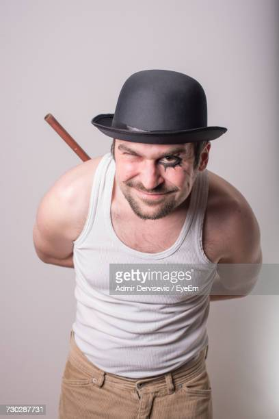 Portrait Of Criminal In Top Hat Winking While Hiding Stick Against White Background