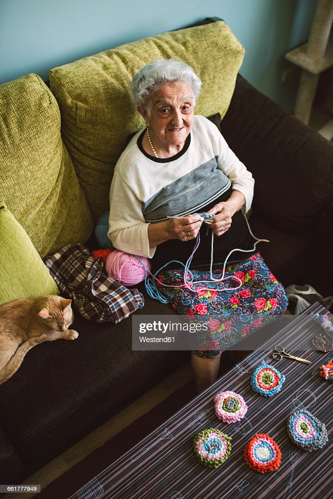 Portrait of crocheting senior woman sitting on couch beside her sleeping cat : Stock Photo