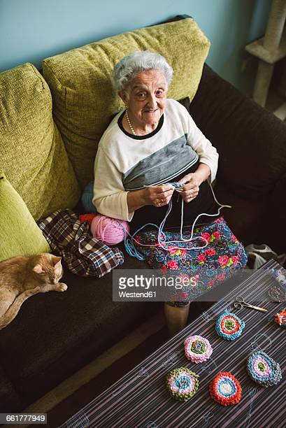 Portrait of crocheting senior woman sitting on couch beside her sleeping cat