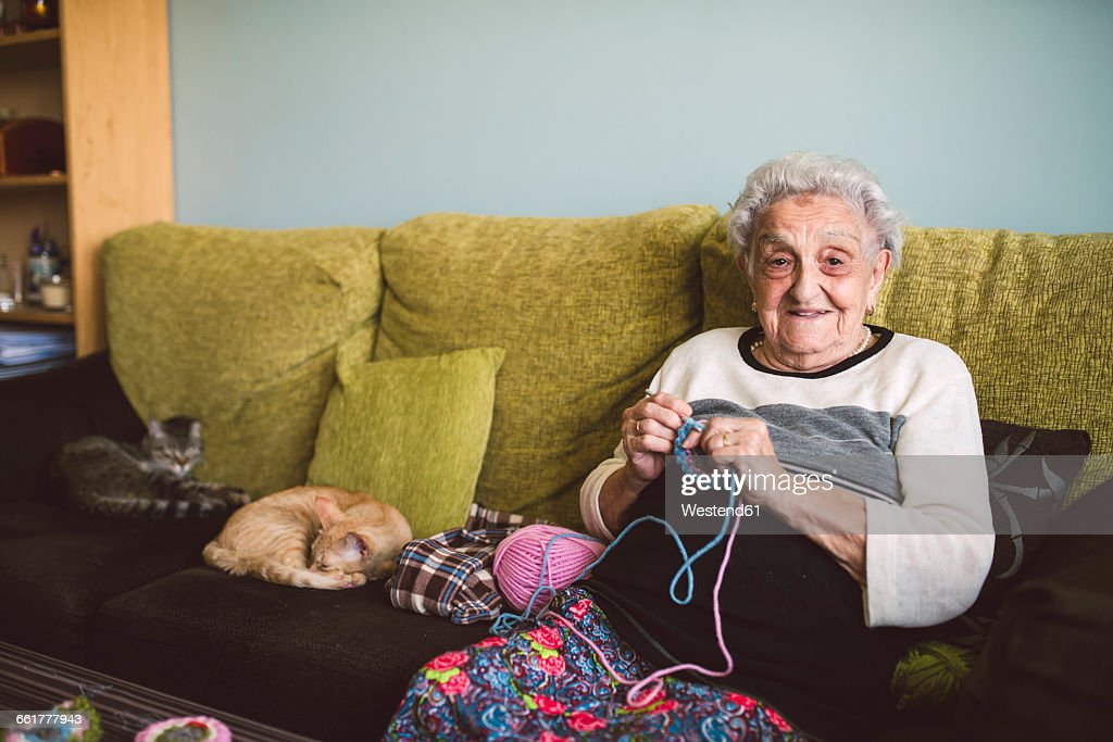 Portrait of crocheting senior woman sitting on couch besides her sleeping cats : Stock Photo