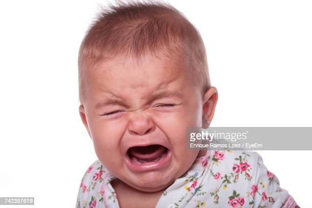 Portrait Of Crying Baby Against White Background