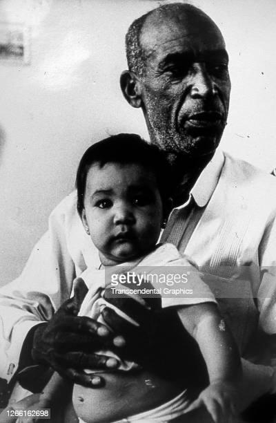 Portrait of Cuban baseball player Martin Dihigo as he poses with his grandson, Matanzas, Cuba, early to mid 1940s.