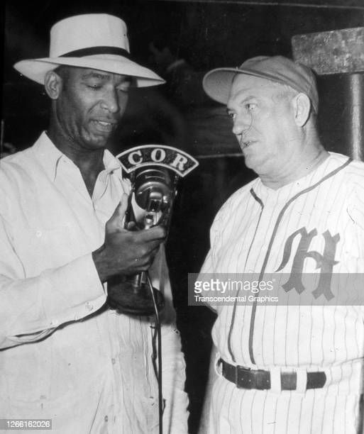 Portrait of Cuban baseball players Martin Dihigo , who holds a microphone, and Mike Gonzalez as they attend an unspecified event, Havana, Cuba, mid...