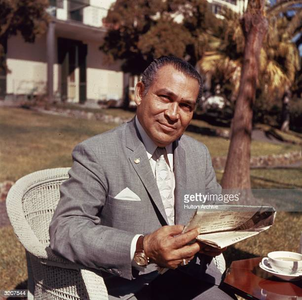 Portrait of Cuban soldier and dictator Fulgencio Batista Former President of Cuba holding a newspaper outdoors