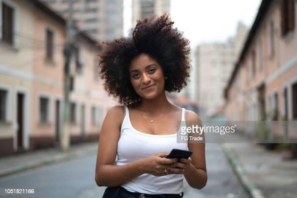 portret van krullend haar vrouw met behulp van mobiele telefoon op straat - mobile stockfoto's en -beelden