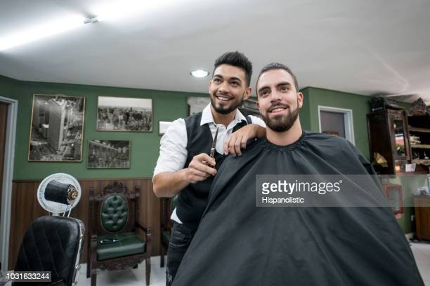 portrait of customer and barber looking at the mirror smiling - hispanolistic stock photos and pictures