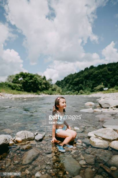 Portrait of cute 4 year old girl playing in river, Niigata, Japan