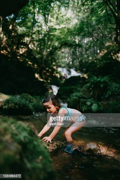 Portrait of cute 4 year old girl playing in river water in forest
