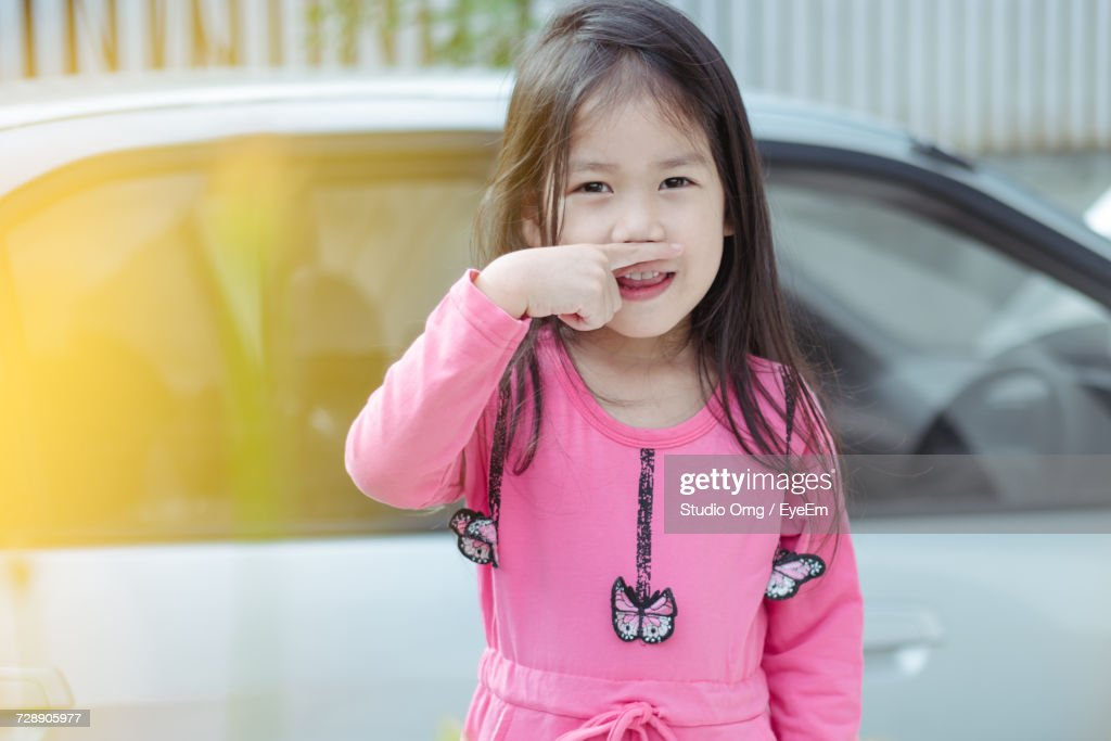 Portrait Of Cute Asian Girl With Finger Under Nose Stock Photo