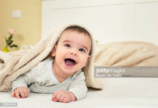 Portrait Of Cute Baby Boy Lying On Bed