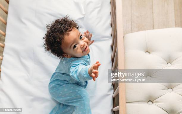 portrait of cute baby boy standing in crib at home - one baby boy only stock pictures, royalty-free photos & images