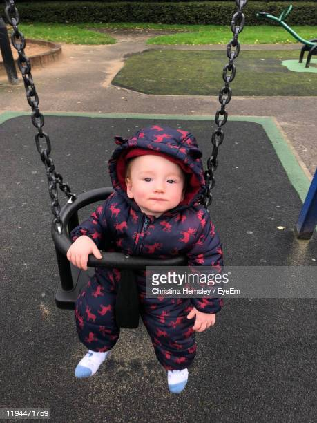 portrait of cute baby boy swinging in playground - one baby boy only stock pictures, royalty-free photos & images