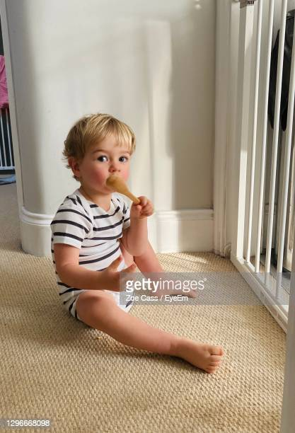 portrait of cute baby boy with spoon sitting on carpet at home - babyhood stock pictures, royalty-free photos & images