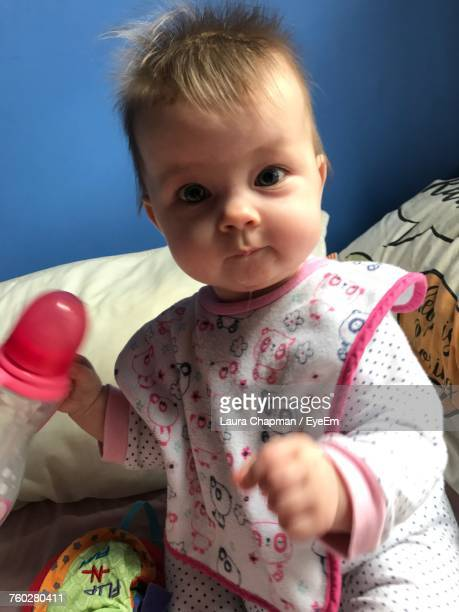 Portrait Of Cute Baby Girl Holding Milk Bottle On Bed At Home