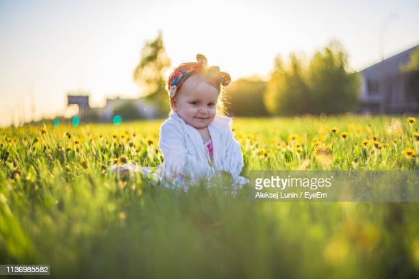 portrait of cute baby girl sitting by plants on land during sunset - lunin stock photos and pictures