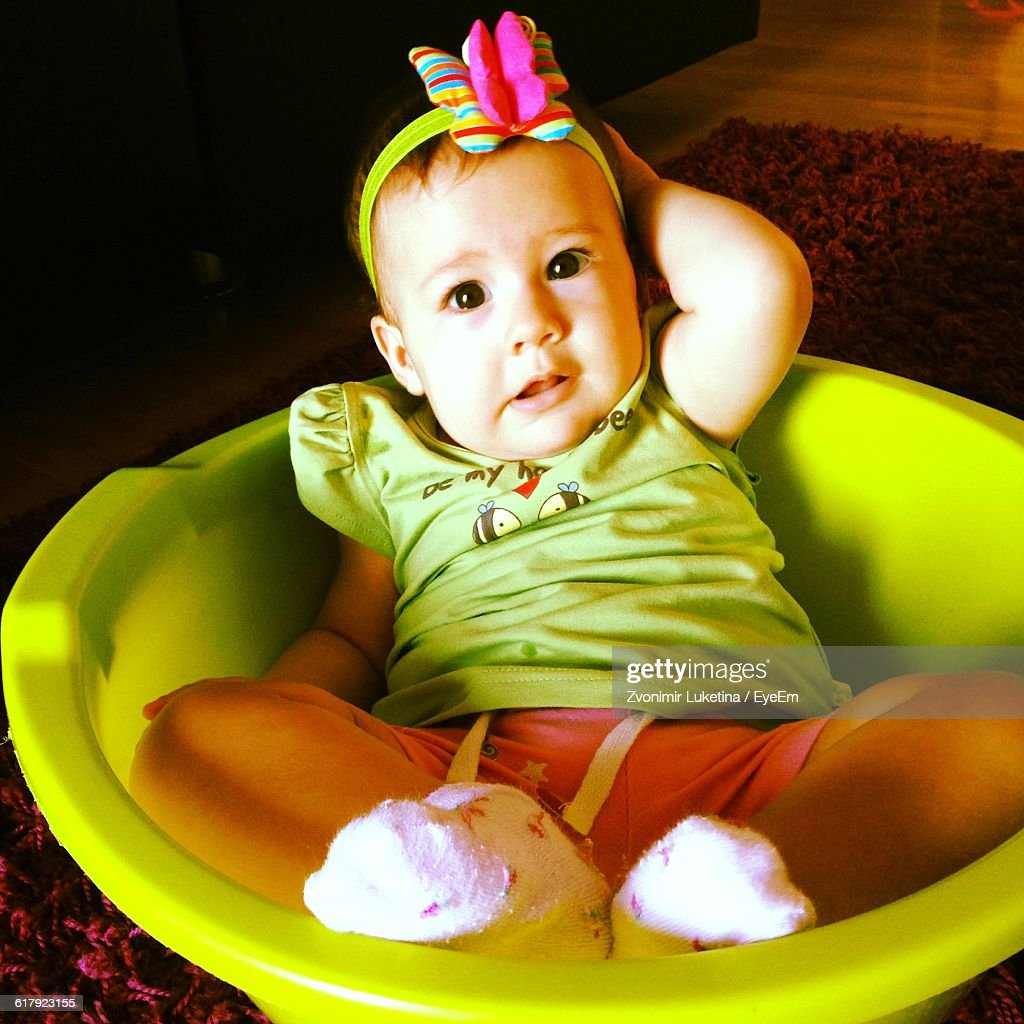 55ce76af2 Portrait Of Cute Baby Girl Sitting In Basket Stock Photo