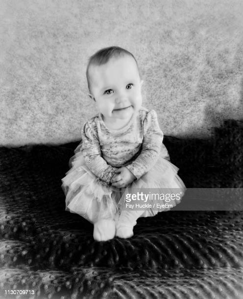 Portrait Of Cute Baby Girl Sitting On Bed Against Wall At Home