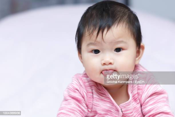 Portrait Of Cute Baby Girl Sticking Out Tongue