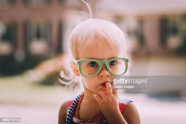 Portrait of cute baby girl wearing eyeglasses with finger in mouth