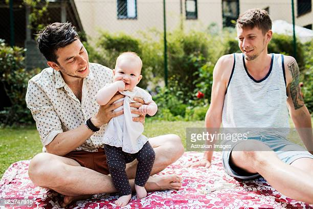 Portrait of cute baby girl with gay couple at yard