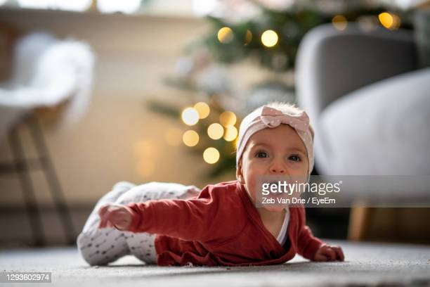 portrait of cute baby girl with mouth open lying on carpet - drie personen stock-fotos und bilder