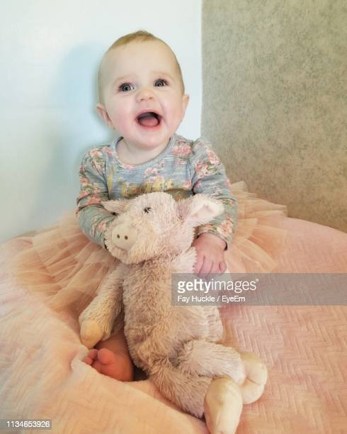 Portrait Of Cute Baby Girl With Toy Sitting On Bed At Home