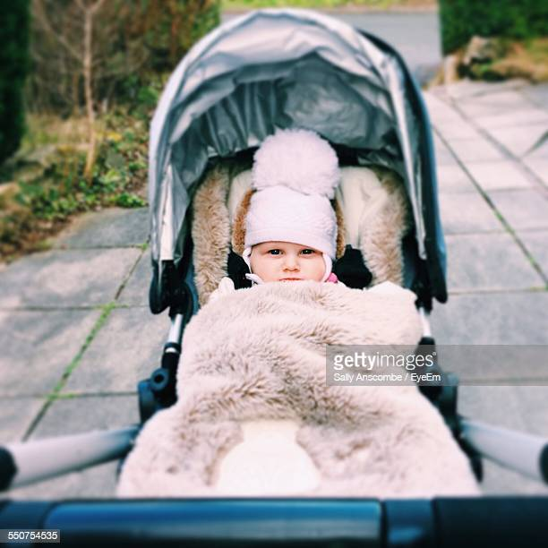 Portrait Of Cute Baby In Carriage On Street