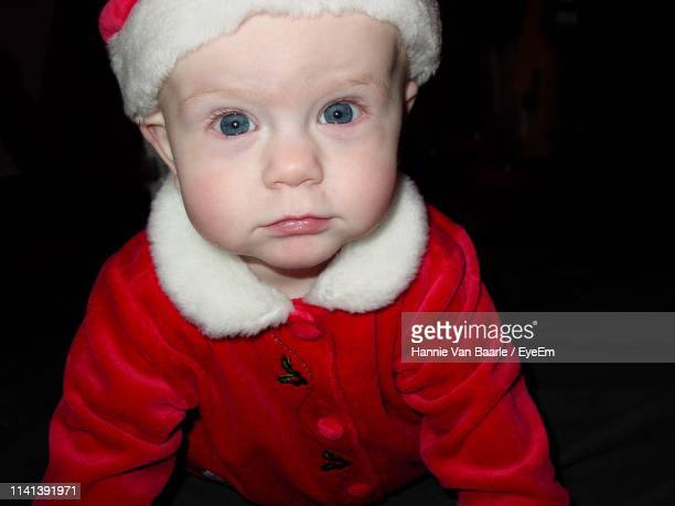 Portrait Of Cute Baby In Santa Claus Costume Against Black Background