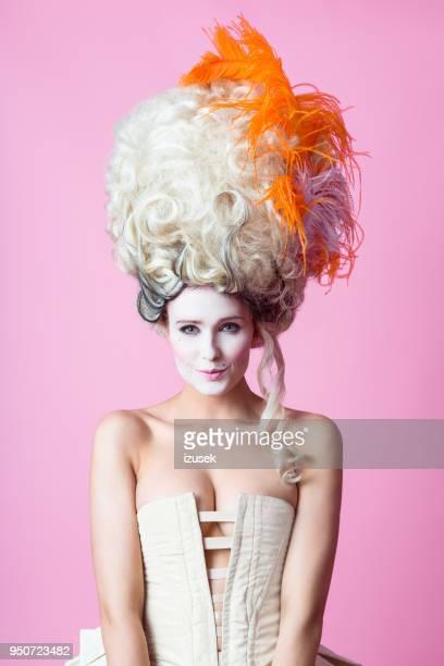 Portrait de femme baroque mignon portant perruque, rose backgroud