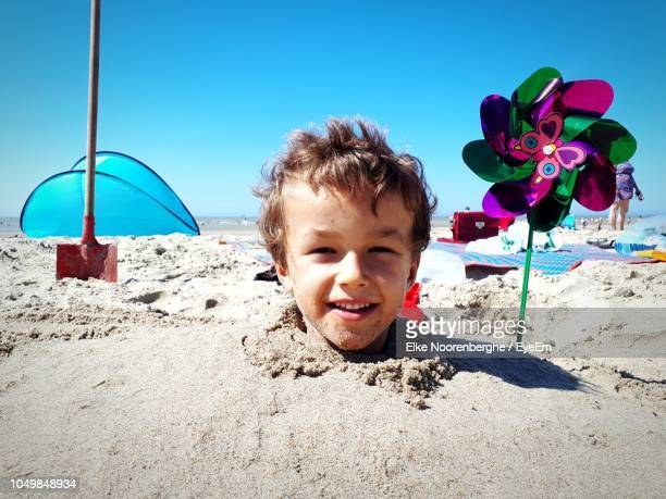 portrait of cute boy buried in sand at beach against sky during sunny day - buried stock pictures, royalty-free photos & images