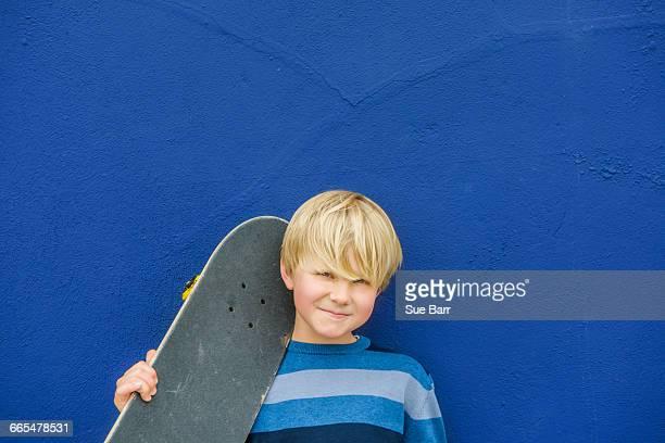 Portrait of cute boy carrying skateboard on shoulder in front of blue wall