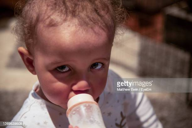 portrait of cute boy drinking from bottle - one baby boy only stock pictures, royalty-free photos & images