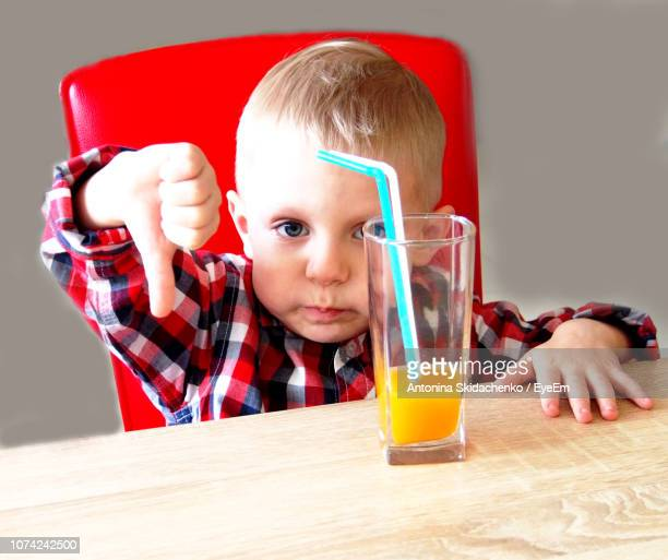 Portrait Of Cute Boy Gesturing Thumbs Down Sign While Sitting By Juice At Restaurant