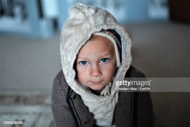 portrait of cute boy in hood at home - christian hilse stock-fotos und bilder